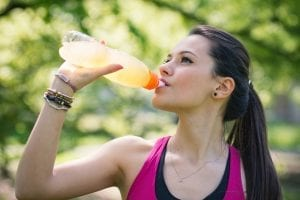 Young woman drinking energy drink outdoors in a park.