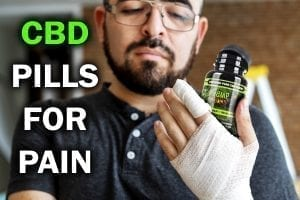 a man with a bandaged hand takes cbd pills for pain from hemp bombs